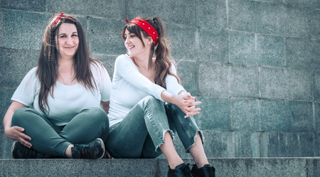 two girls in jeans and a white T-shirt, against the wall background, the concept of urban clothing, female friendship and youth style