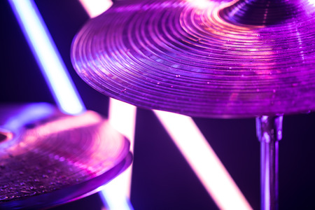 drum cymbal close-up, with drumsticks on a background of colored lanterns. Water drops on plates.