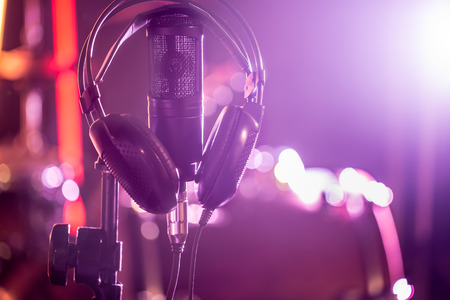Studio microphone and headphones on a close-up stand, in a recording Studio or concert hall. Beautiful blurred background of colored lights. A musical concept. 写真素材