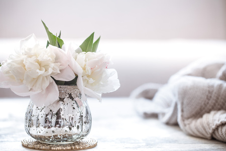 composition with a vase and peonies on a wooden background, the concept of home comfort and interior Stock Photo