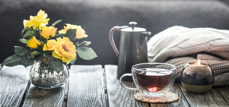 cup of tea with a teapot and roses in a vase, stand in the living room at home on a wooden table