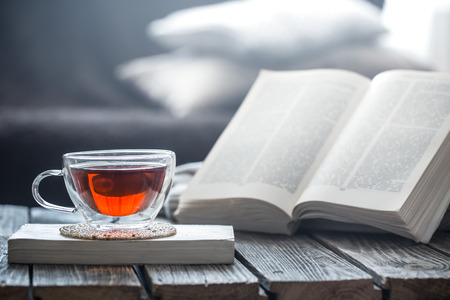 still life a cup of tea with an open book on a wooden table, the concept of coziness and reading