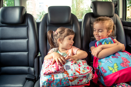 Children in the car go to school, happy, sweet faces of sisters, pupils of a kindergarten with school backpacks, sitting in the parental car Standard-Bild