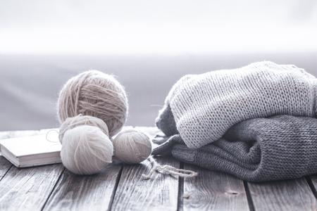 Loisirs à la maison, chandails tricotés confortables avec une pelote de laine dans le salon sur un fond en bois