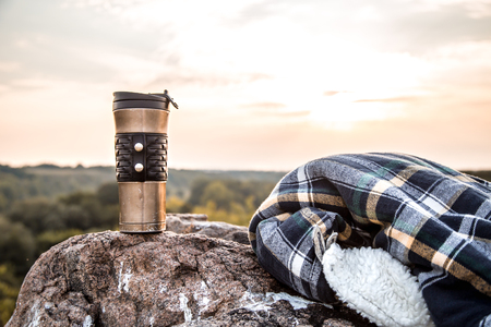 camping items, tumbler with jacket on a stone on the background of nature, the concept of travel and recreation