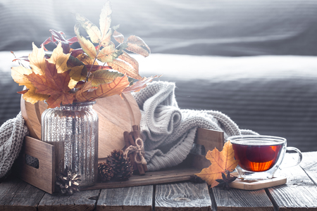 Autumn composition with elements of home decor with leaves in the interior of the living room, the concept of home comfort