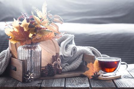 Herbstkomposition mit Elementen der Wohnkultur mit Blättern im Inneren des Wohnzimmers, das Konzept des Wohnkomforts Standard-Bild