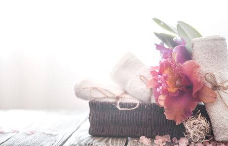 Spa items in a wicker stand on a light background with a tropical orchid, body care concept 写真素材
