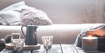 still life from home interior on a wooden background with a candle and a small kettle with a beautiful glass, home comfort concept Banque d'images - 112485740