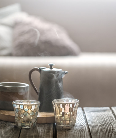 still life from home interior on a wooden background with a small kettle and a beautiful glass, home comfort concept Stock fotó