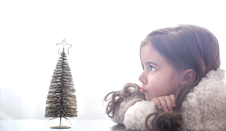 new year background with a little girl and a small Christmas tree on the table, a place for text, festive new year concept Фото со стока