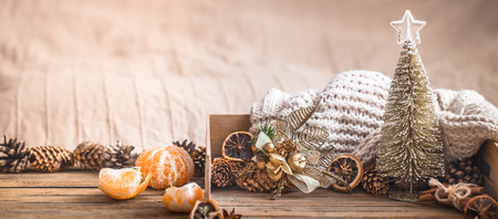 Festive Christmas cozy atmosphere with home decor and tangerines on a wooden background, home comfort concept