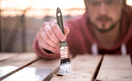 A man paints with white paint on wooden planks. Man in industrial concept. There is a place for text, the object is close up
