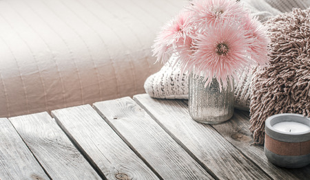 still life from home interior on a wooden background with a candle and pillows, home comfort concept Imagens