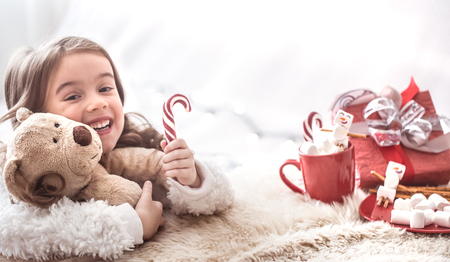 Christmas concept, little cute girl hugging Teddy bear toy in living room with gifts on light background, place for text 스톡 콘텐츠