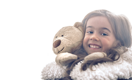 Little beautiful cute girl hugs a Teddy bear toy on a light background, a place for text