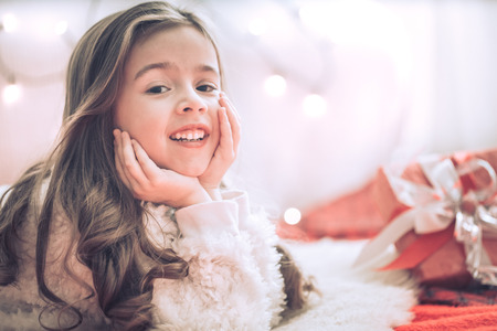 Christmas and holiday concept-cute little girl with a gift in a red box