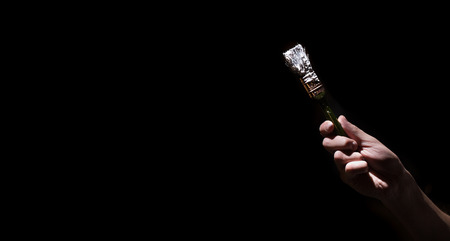 male hand holding a brush with white paint on a black background. Man in industrial concept. there is a place for text, object close up