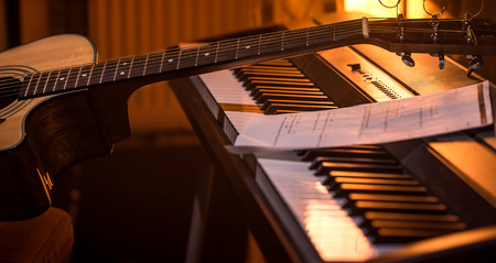 acoustic guitar stands on piano with notes, close-up, beautiful color background, music activity concept Foto de archivo