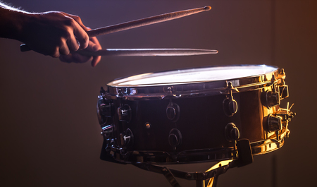 man playing the snare drum on a beautiful colored background, the concept of musical instruments Stock Photo