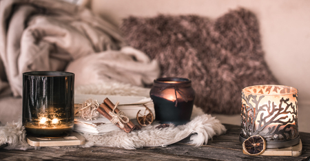 still life home atmosphere in the interior with candles and a book on the background of cozy bedspreads, home decor elements, the concept of comfort and coziness