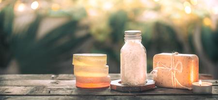 Savon artisanal de spa au sel de mer, composition sur des feuilles tropicales avec une bougie, fond en bois avec une place pour le texte, concept de spa et relaxation pour le corps