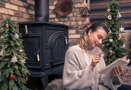 girl reading a book in a cozy home atmosphere near the fireplace, the concept of home rest Banco de Imagens