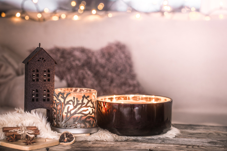 home still life in the interior with beautiful candles, on the background of a cozy home decor, the concept of home items