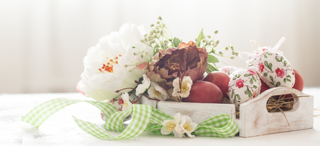 Easter background with a basket and red eggs with flowers, the bright interior, the concept of the Easter holidays