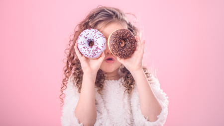 Portrait of a little surprised girl with curly hair, and two mouth-watering donuts in her hands, closes her eyes with donuts, on a pink background 版權商用圖片