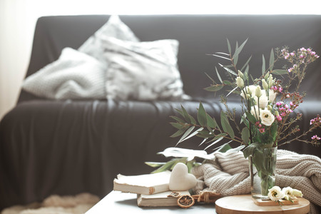 Cozy home interior living room with a black sofa and a vase with flowers and decor items on a small table