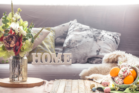 Easter breakfast in a homely interior with a vase of flowers and wooden letters home, concept of Holidays and home comfort