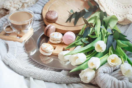 Still-life morning breakfast with coffee and macaroon on the background of a bed with white tulips, concept of womens day