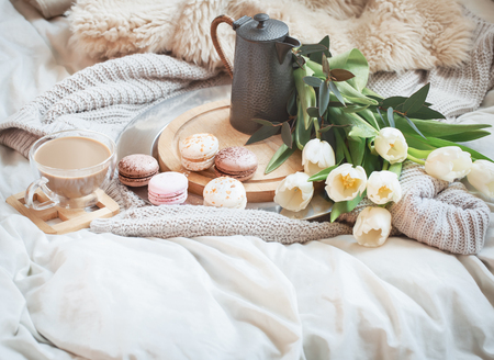 Still-life morning breakfast with coffee and macaroon on the background of a bed with white tulips, concept of women's day