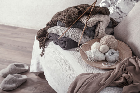 Vintage wooden knitting needles and threads on a cozy sofa with pillows and Slippers nearby. Still life photo. The concept of comfort