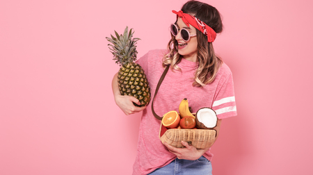Horizontal portrait of hipster girl in stylish clothes with sunglasses, with healthy food, fruits, on pink background, lifestyle concept Stock fotó
