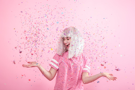 Funny Girl with silver hair gives a smile and emotion on pink background. Young woman or teen girl with confetti. Concept of holiday and party.