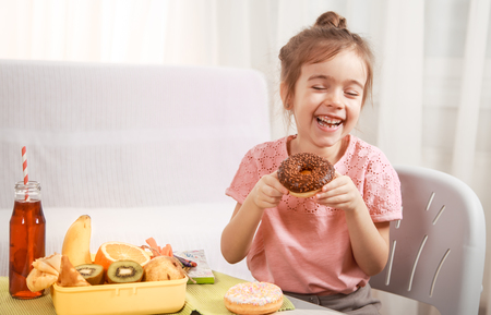 Little beautiful cheerful girl eating a donut and lunch box with fruits at home at the table, the concept of children's food