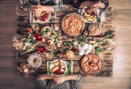 A traditional celebration of the Passover, the feast of the Passover. Apartment-holiday friends or family at the festive table top view. Friends pray in honor of Easter at the festive table.