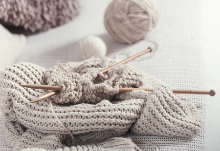 Vintage wooden knitting needles and yarn on the cosy sofa with a sweater ,with a soft focus . Still life photo. The concept of comfort