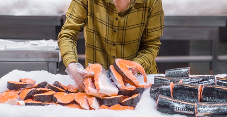 Woman in the supermarket. Beautiful young woman holding a salmon fish in her hands. The concept of healthy eating. Seafood
