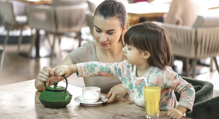 Mum with a small cute daughter drink tea and orange juice in a cafe, the concept of family values and family