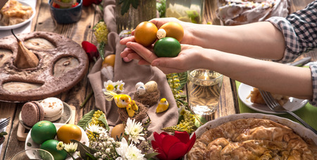 Home Holiday friends or family at the festive Easter table with Easter colored eggs. The concept of the celebration