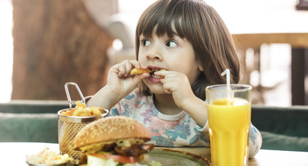 Little cute girl eating a fast food sandwich with fries and orange juice in a cafe. Fast food concept.