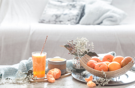 Freshly-grown organic fresh orange juice in the interior of the house, with a turquoise blanket and a basket of fruit. Healthy food. Vitamin C