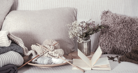 Vintage wooden knitting needles and threads on a cozy sofa with pillows and a vase of flowers. Open book for reading. Still life photo. The concept of comfort