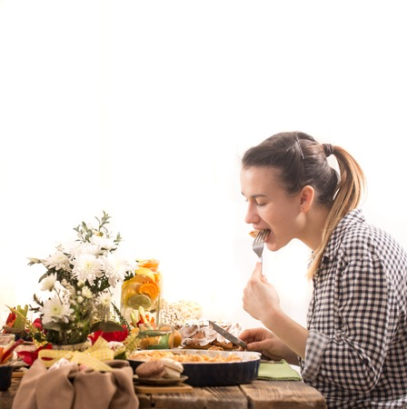 young woman eating at the festive Easter table , the concept of the celebration Imagens