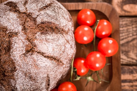 Fresh dark round bread on a wooden plate with small tomatoes closeup, food concept