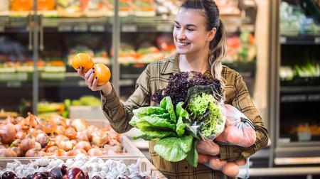 Kobieta w supermarkecie. Piękna młoda kobieta zakupy w supermarkecie i kupowanie świeżych organicznych warzyw. Pojęcie zdrowego odżywiania. Zbiór