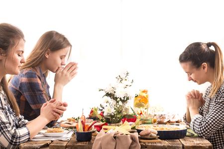 Home Urlaubsfreunde oder Familie am festlichen Ostertisch beten vor dem Essen, das Konzept der Feier Standard-Bild